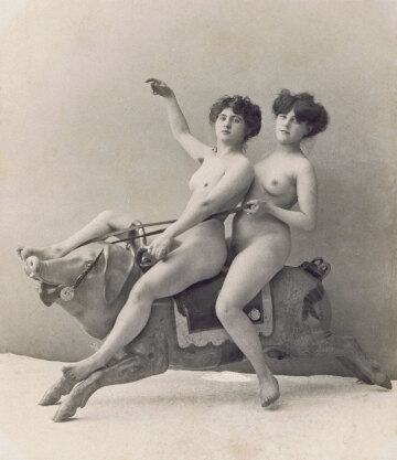 two nude women on a carousel pig, around 1900.
